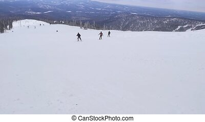 Snowboarder sits high in the mountains on the edge of the...