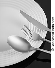 Fork, spoon and knife on a plate