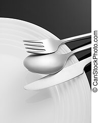 Place setting - Fork, spoon, knife and plate on black...