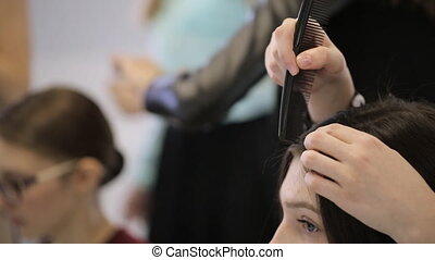 In model school one woman is making hairstyle to another....