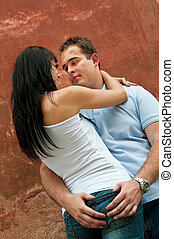 Intimate moments - young couple at wall - Young couple in...