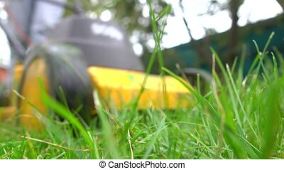 Yellow lawn mower in action, close up. 4K low angle 4K shot...