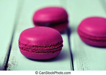 purple macarons on a pale blue rustic surface