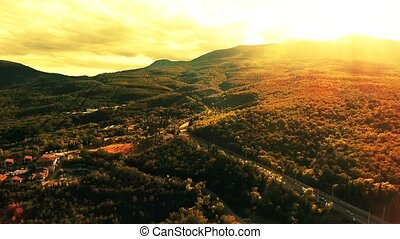 Aerial view on sunset and the road in the mountains to sea...