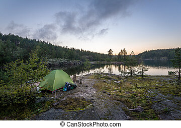 Tourist tent in the sunset at rocky island of Ladoga lake.