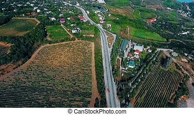 Aerial view on suburban road with cars, trucks and other tranportation in a mountains