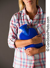 Young Woman Holding Hot Water Bottle Against Stomach