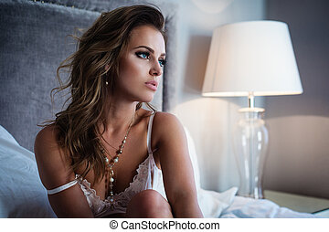 Sexy lingerie in bed - Beautiful lady in sexy lingerie sits...