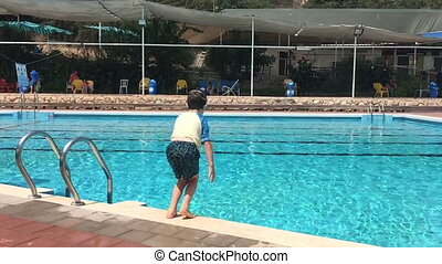 Jumping into a swimming pool in slow motion - Young boy jump...