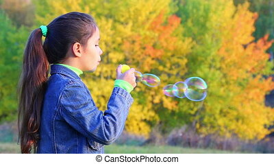 Girl blowing up a soap bubbles - Little girl blowing up a...