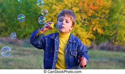 handsome boy blowing a soap bubbles on the autumn landscape