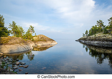 Mirror water and stone shores of Karelia republic islands -...