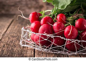 Fresh rustic harvest of radishes healthy vegetables in vintage basket background