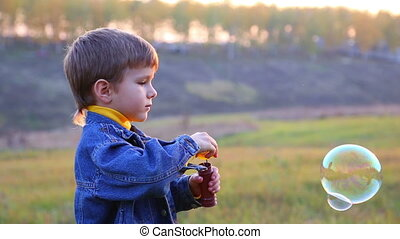 Boy blowing a soap bubbles - Little boy blowing a soap...