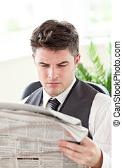 Concentrated businessman reading a newspaper