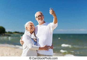 happy senior couple hugging on summer beach