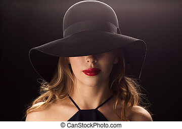 beautiful woman in black hat over dark background - people,...