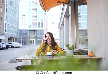 happy woman calling on smartphone at city cafe -...