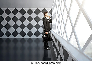 Thoughtful businessman in chessboard interior - Thoughtful...