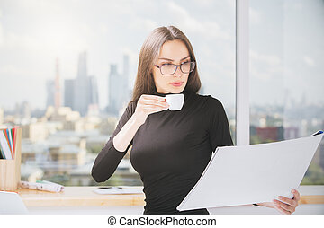 Woman drinking coffee, doing paperwork - Portrait of...