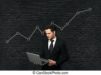 Growing line chart - Young businessman in suit using laptop...
