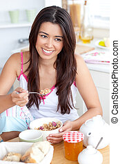 Smiling woman eating muesli with fruits sitting in the...