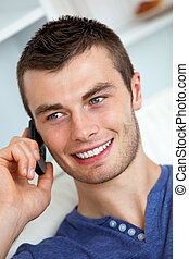 Handsome young man talking on phone in living room