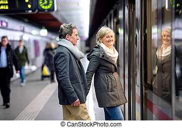 Senior couple standing at the underground platform, waiting...