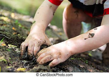 Little Child's Hands Digging in the Mud - The Dirty hands of...