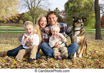 Happy Family of Four People and Dog OUtside in Autumn