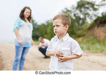 Family holiday on the river bank - Boy throwing rocks into...
