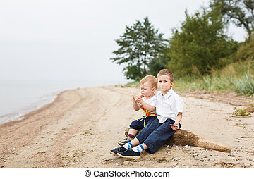 Holiday on the river bank - Two brothers sitting on a bank...