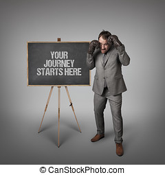 Your journey starts here text on blackboard with businessman...