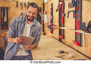 Handsome carpenter working - Handsome carpenter is using a...