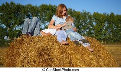 mother with children playing on a haystack in the sun