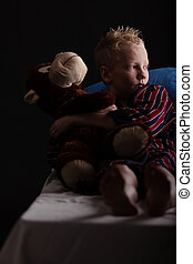 Relaxing little boy sitting with plush toy while looking...