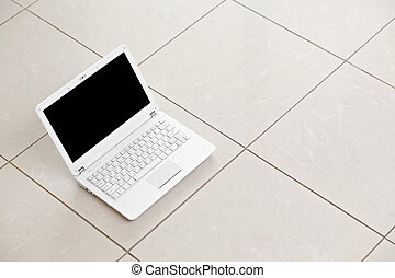 White laptop on bright tiled floor. - White laptop on bright...