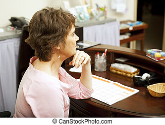 Bored Store Clerk - Bored store clerk sitting at her desk No...