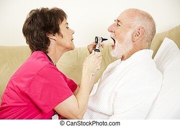 Home Nurse Examines Throat - Home health care nurse uses an...