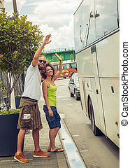 Young couple waving goodbye to their friends on the bus at...