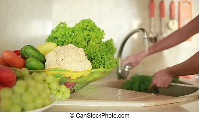 girl washes grapes. vegetables on the kitchen table. tomatoes and cabbage