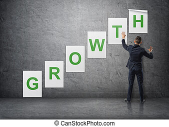 Businessman putting up posters with letters on concrete wall that form 'growth' word