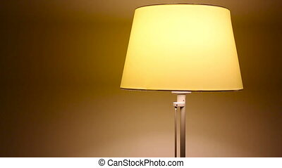 dancing yellow small bedside lamp in the apartment