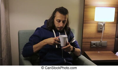 guy sits down, takes a Cup of tea from the bedside and drink it
