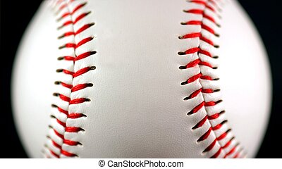 Baseball - white leather baseball with red stitching on...