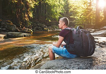 Sunset in pure nature. Traveler with backpack resting on the...