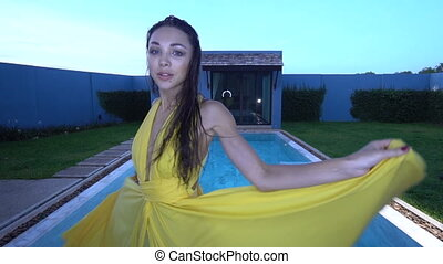 Beautiful brunette woman in yellow dress by the pool -...