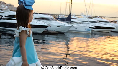 portrait of a little girl three years with the blue bow on her head, stands near the water