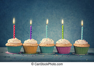 Cupcakes with dotted candles on a blue background