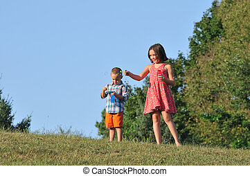 brother and sister blowing bubbles - Happy litte brother and...